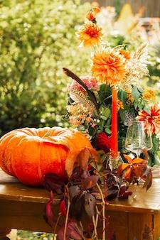 Herbstromantische kulisse: blumenstrauß aus dahlien, granatäpfeln, kerzen, kürbissen und gläsern