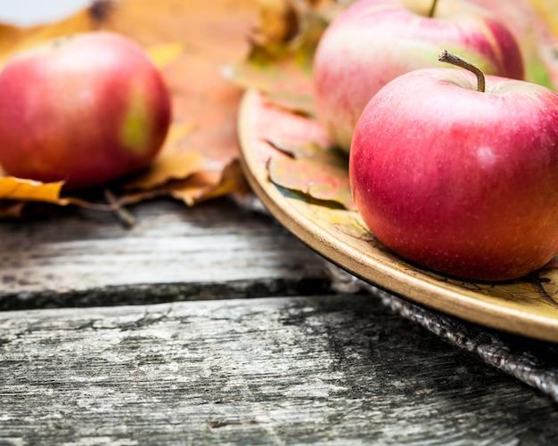 Herbstrote äpfel und ahornblätter auf altem holztisch thanksgiving day konzept