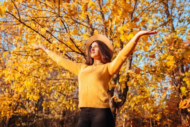 Herbstsaison aktivitäten. werfende blätter der frau im herbstwald. junge frau, die spaß draußen hat