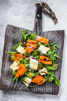 Herbstsalat mit gebackenem kürbis und brie-käse. gesundes veganes lebensmittelkonzept. weißer hintergrund. ansicht von oben.