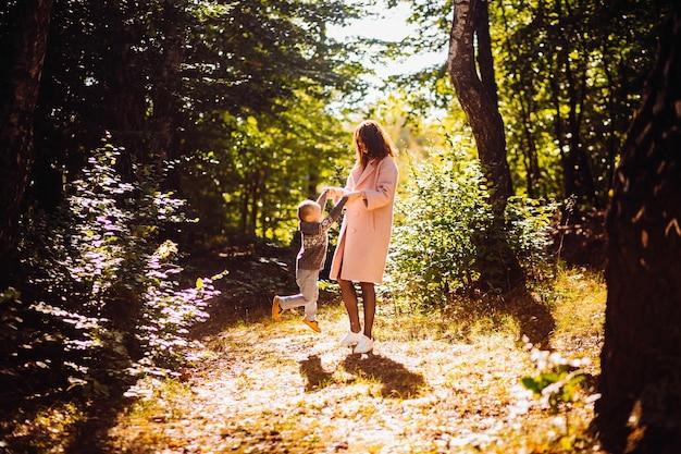 Herbstsonne scheint um die mama und sohn, die im park aufwerfen