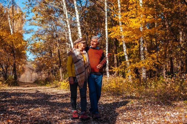 Herbstspaziergang. ältere paare, die in fallpark gehen. glücklicher mann und frau, die draußen spricht und sich entspannt