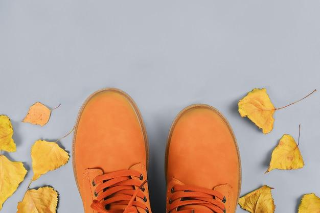 Herbststiefel der orange braunmänner auf grauem pastell