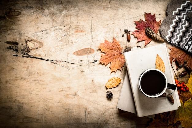Herbststil. kaffee mit alten büchern. auf hölzernem hintergrund.
