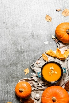 Herbststil. kürbissuppe von einem reifen kürbis auf steintisch.
