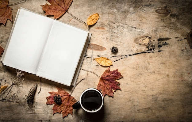 Herbststil. öffnen sie das buch mit einer heißen tasse kaffee. auf hölzernem hintergrund.