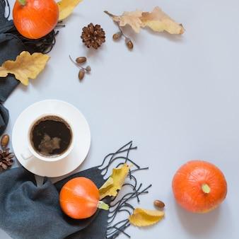 Herbststilleben, schwarzer kaffee, grauer schal und kürbis.