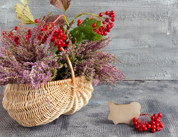 Herbststillleben auf betonhintergrundkorb mit heidekraut und viburnum und leerer postkartendanke...