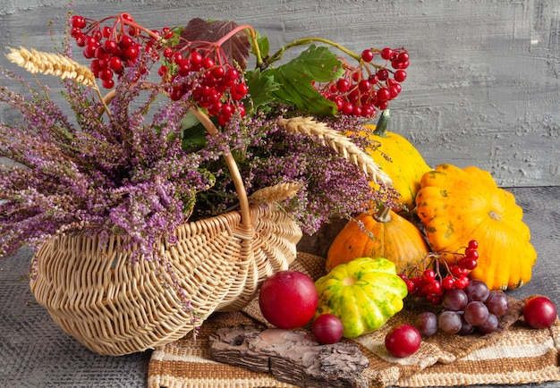Herbststillleben auf einem konkreten hintergrundkorb mit heidekraut viburnum und früchten thanksgiving day