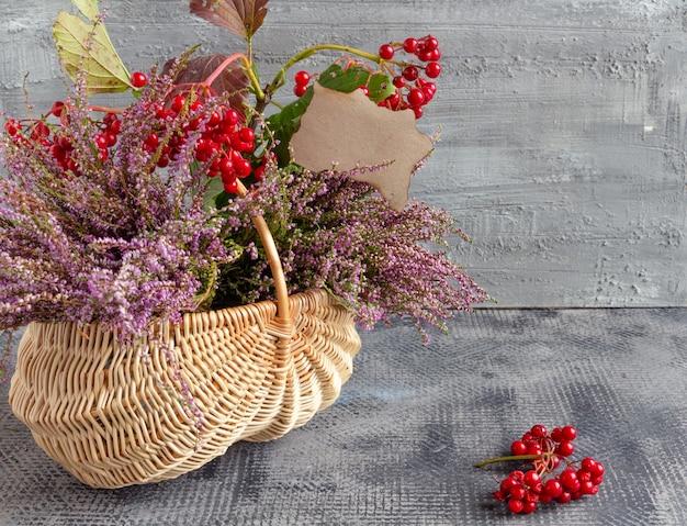 Herbststillleben auf konkretem hintergrundkorb mit heather viburnum postkarte thanksgiving day