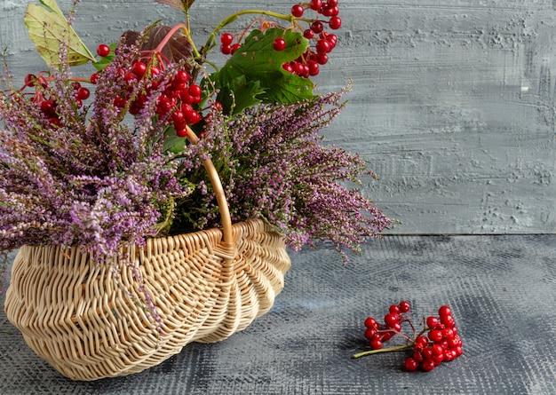 Herbststillleben auf konkretem hintergrundkorb mit heidekraut und viburnum-danksagungskopienraum