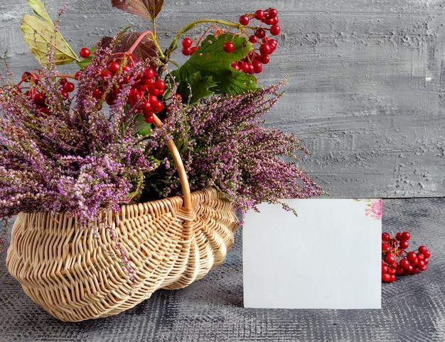 Herbststillleben auf konkretem hintergrundkorb mit heidekraut und viburnum und leerer postkarte