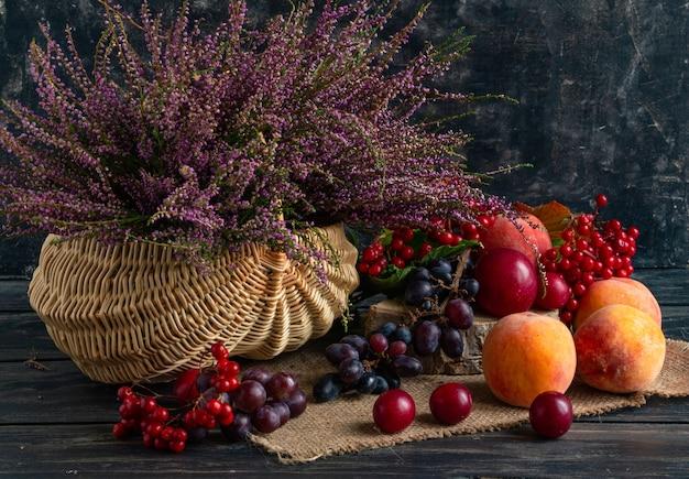 Herbststillleben auf schwarzem hintergrundkorb mit heidekraut und viburnum und früchten