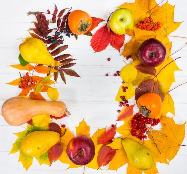 Herbststillleben der ernte mit blättern auf weißem holzschreibtisch mit kopienraum.