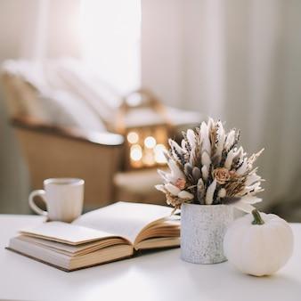 Herbststillleben. kaffeetasse, blumen, buch und kürbis.