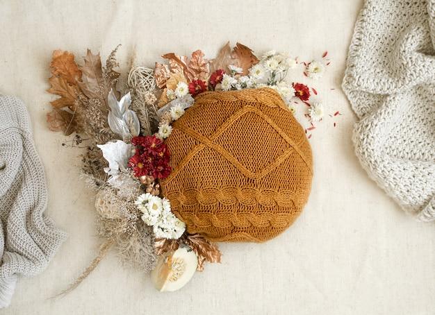 Herbststillleben mit blumen und strickelementen auf einem weißen raum hautnah.