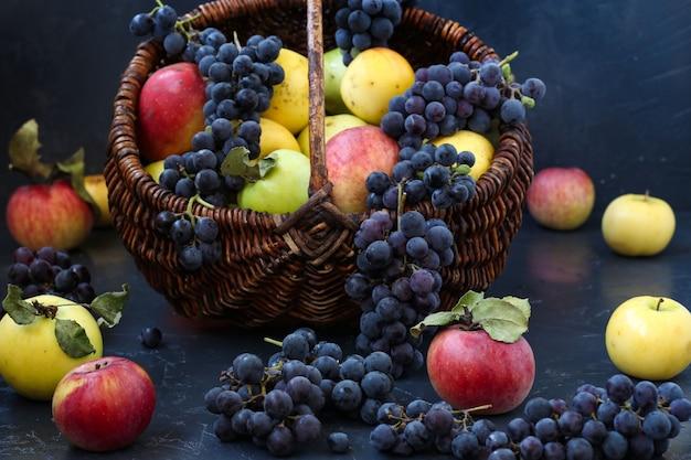 Herbststillleben mit den äpfeln und trauben gelegen, äpfeln und trauben in einem korb