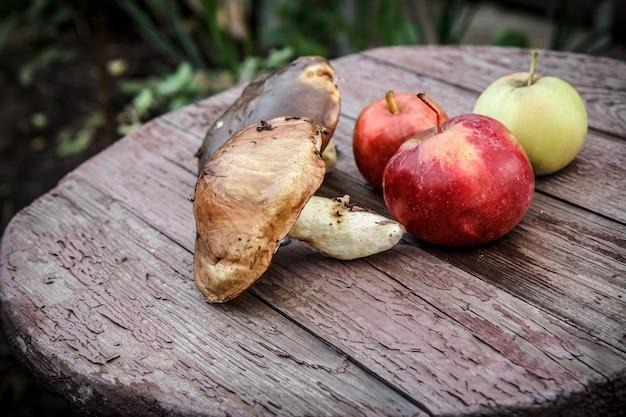 Herbststillleben mit einem pilz und äpfeln auf den holzbrettern.