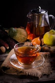 Herbststillleben mit glasteekanne und tasse tee auf sackleinen