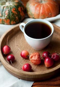 Herbststillleben mit kaffee, kürbis, physalis und kleinen roten äpfeln