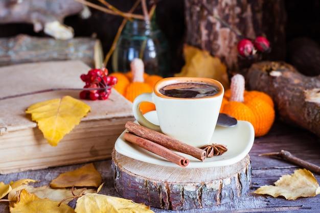 Herbststillleben mit kaffeegetränk. eine tasse schwarzen kaffee und zimt auf einem schnitt eines baumes.