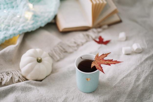 Herbststillleben mit kaffeetasse blumen und kürbissen auf einem gemütlichen plaid