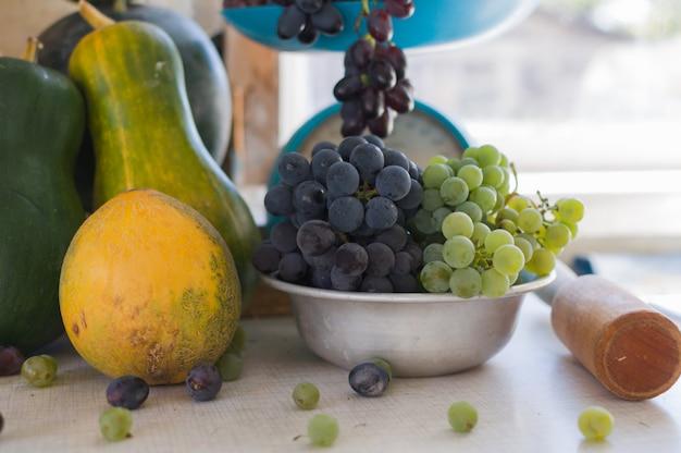 Herbststillleben mit kürbissen, melonen, wassermelonen, trauben auf einer waage und in einer metallschale auf einem weißen holztisch. herbsterntekonzept.