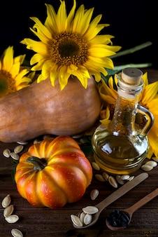 Herbststillleben mit kürbissen, öl und sonnenblumen