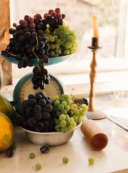 Herbststillleben mit kürbissen und trauben in einer metallschale, trauben auf einem weißen holztisch verteilt. im hintergrund ist eine kerze in einem kerzenhalter. herbsterntekonzept.