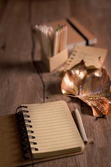 Herbststillleben mit leerem offenem notizbuch und gemaltem trockenem blatt
