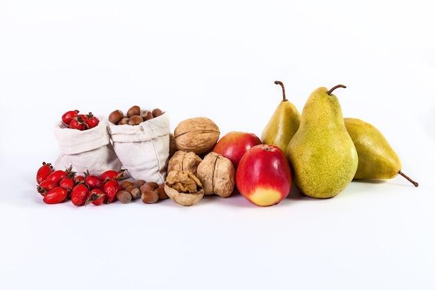 Herbststillleben mit obst äpfel birnen nüsse hagebutten isoliert auf weißem hintergrund