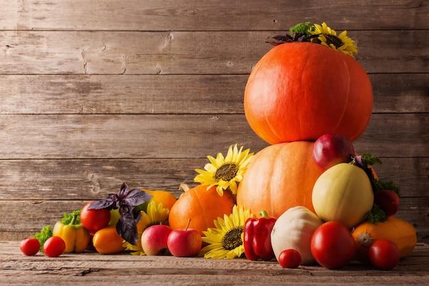 Herbststillleben mit saisonalen früchten, gemüse und blumen