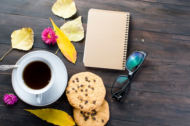 Herbststillleben mit tasse tee, plätzchen, gläsern und blättern.