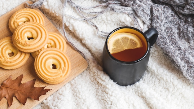 Herbststillleben mit tasse tee, plätzchen, strickjacke und blättern auf einer warmen weichen decke.