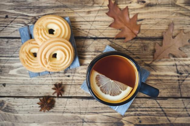Herbststillleben mit tasse tee, plätzchen, strickjacke und blättern auf holzoberfläche.
