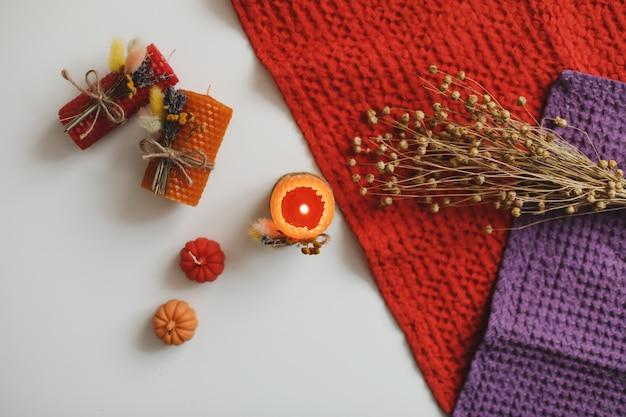 Herbststillleben und gemütliche wohnkultur mit kerzen und textilem hygge-lifestyle