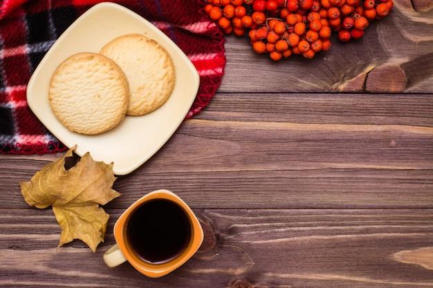 Herbststilllebenkaffee, plätzchen, ein plaid, ein notizbuch und ein bleistift auf hölzerner draufsicht