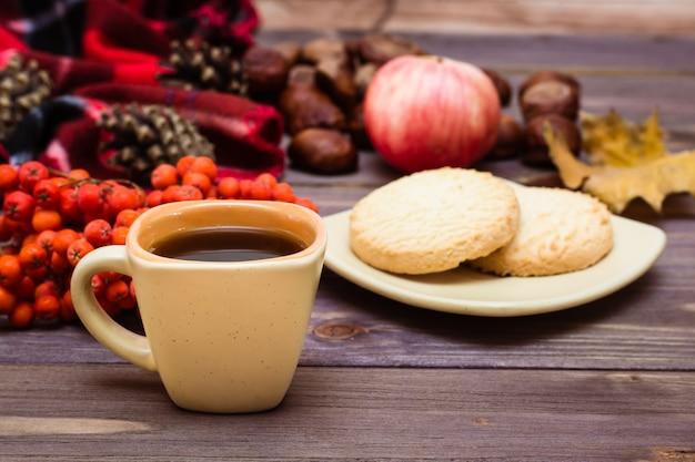 Herbststilllebenkaffee, plätzchen, ein plaid, ein notizbuch und ein bleistift auf holz