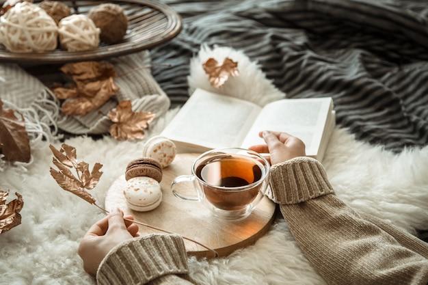 Herbststilllebenmädchen, das eine tasse tee hält.