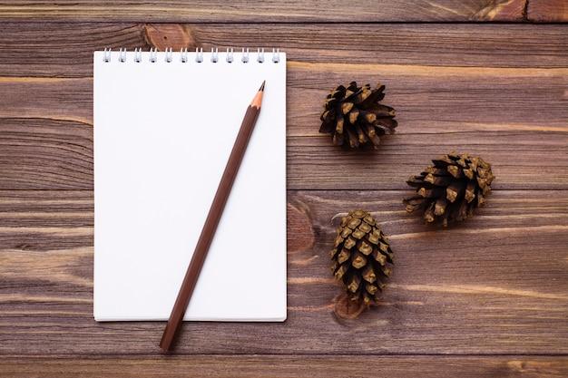 Herbststilllebennotizbuch, -bleistift und -kegel auf hölzerner draufsicht
