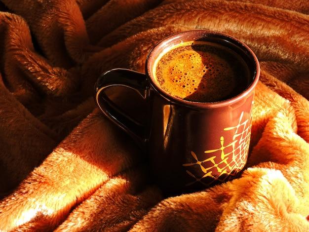 Herbststimmung. eine tasse kaffee auf einem braunen plaid.