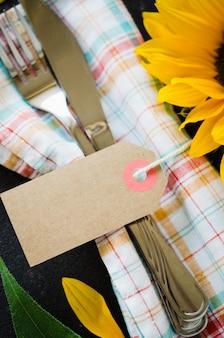Herbsttabellengedeck mit empty tag, tischbesteck mit serviette und sonnenblume.