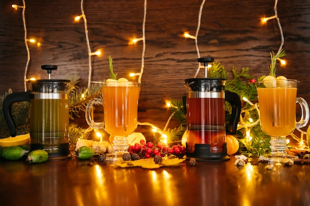 Herbsttee in der französischen presse und zitrus-tee im transparenten becher mit apfel, feijoa und litschi auf dem tisch im restaurant