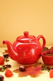 Herbsttee rote teekanne, schale mit tee, ahornblätter, kastanien, physalis auf gelbem hölzernem.