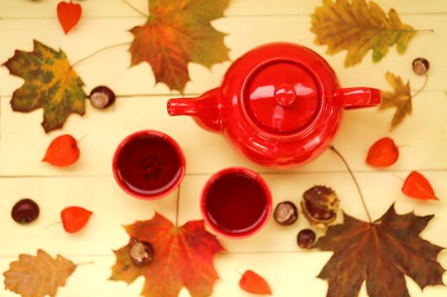 Herbsttee. rote teekanne, tassen mit tee, kastanien, herbstlaub