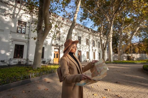 Herbsttourismus. junge attraktive weibliche reisende wird vom stadtplan geführt. schönes mädchen, das richtung in der stadt sucht. urlaubs- und tourismuskonzept