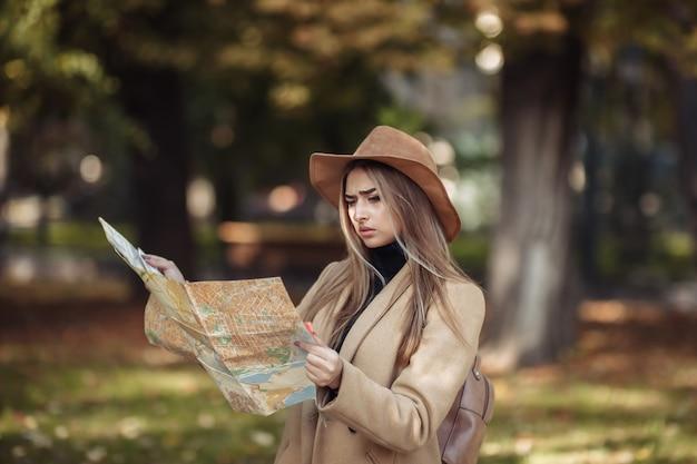 Herbsttourismus. junge attraktive weibliche reisende wird vom stadtplan geführt.
