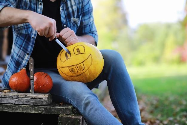 Herbsttraditionen und vorbereitungen für den feiertag halloween. ein haus in der natur, eine lampe aus kürbissen schneidet am tisch aus.
