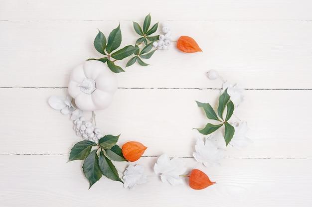 Herbstuntergrenze von weißen kürbisen und von silberblättern