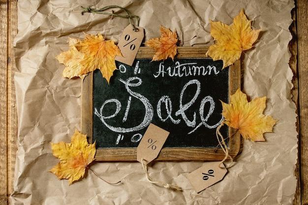 Herbstverkaufskonzept. weinlese-tafel mit handgeschriebener beschriftung verkauf, etiketten mit prozenten, gelbe herbstblätter über handwerklich zerknittertem papier. flach liegen.